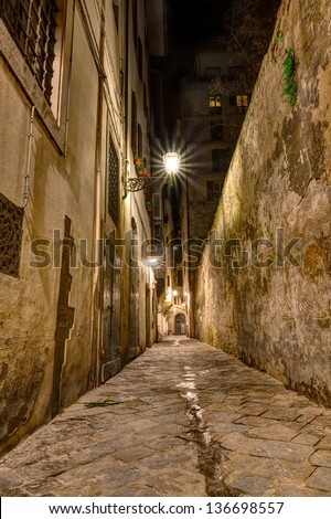 dark narrow alley at night lit by old street lamps in Tuscany, Italy - stock photo