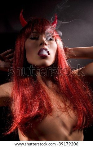 dark picture of smoking naked devil woman - stock photo