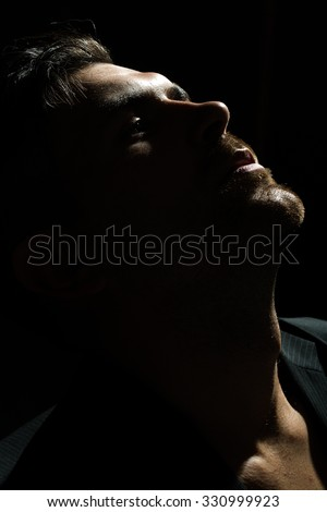 Dark portrait closeup of one young handsome sensual unshaven bearded man model half face stares ahead in studio play of light and shadow on black background, vertical picture - stock photo