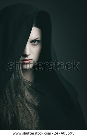 Dark portrait of a beautiful woman with black robe . Halloween and horror concept - stock photo