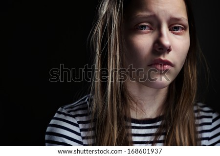 Dark portrait of a crying teen girl, studio shot - stock photo