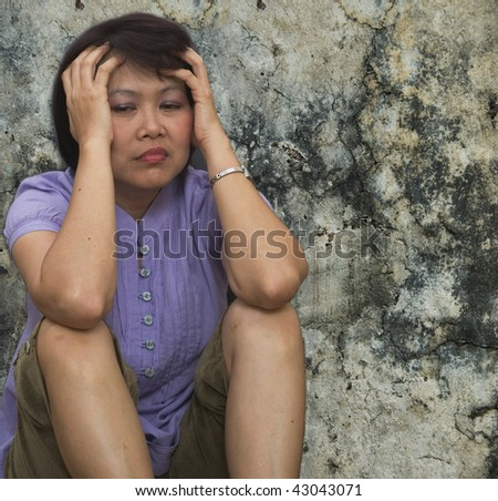 dark portrait of a woman holding her head and feeling depressed - stock photo