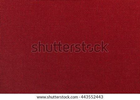 Dark red background from a textile material. Fabric with natural texture. Cloth backdrop. - stock photo