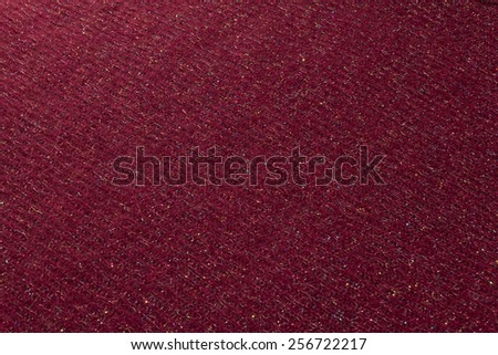 Dark red wool fabric with woven multicolored shiny thread, background - stock photo