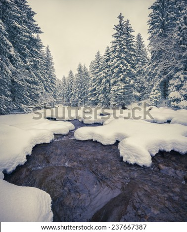 Dark river in the winter mountain forest. Retro style. - stock photo