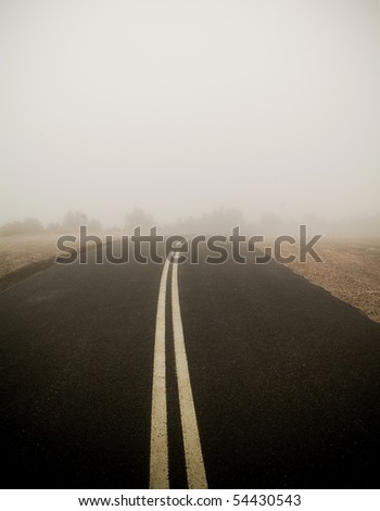 Dark road with double lines disappears into very thick fog - stock photo