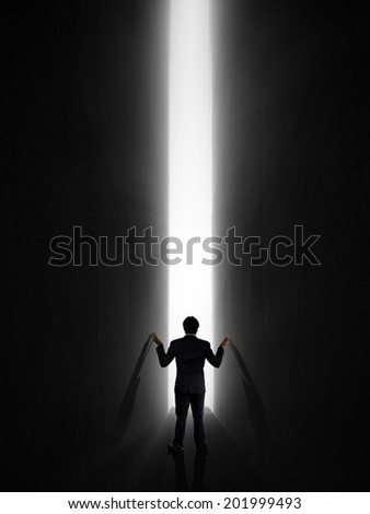 dark room with businessman exit to the light - stock photo