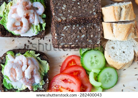 Dark rye bread spiced with caraway seeds and topped with fresh prawns or shrimps. The platter is completed with a sliced French baguette accompanied by tomato and cucumber.  - stock photo