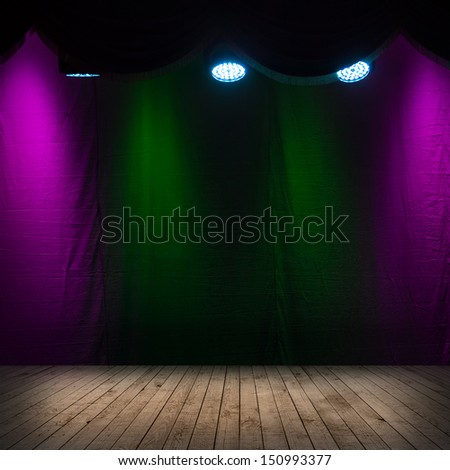 Dark scene interior with spotlights, wooden stage and colorful background - stock photo