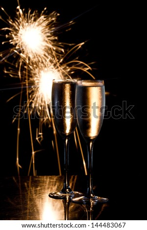 dark scene with two glasses of champagne and fireworks in the background - stock photo
