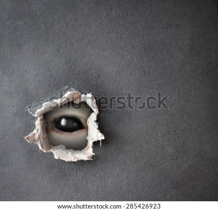 Dark series - a look from darkness. Monster eye in hole in the paper - stock photo