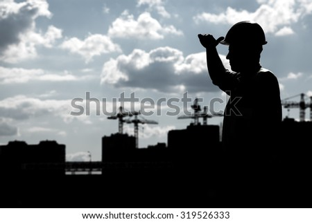 Dark silhouette of a builder on a background of a construction site. - stock photo