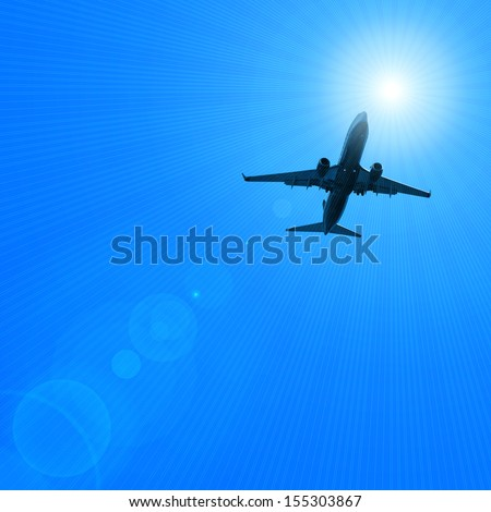 dark silhouette of airplane flying over the blue skies and sun rays background  - stock photo