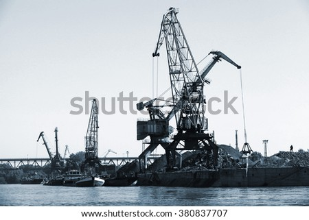 Dark silhouettes of industrial port cranes on Danube River, Bulgaria. Black and white photo - stock photo
