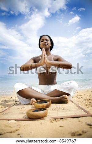dark skinned girl practicing yoga on the beach - stock photo