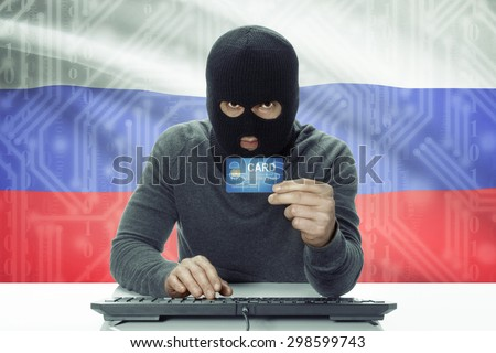 Dark-skinned hacker with credit card and flag on background - Russia - stock photo