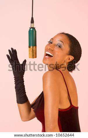dark skinned sexy female sings by microphone - stock photo