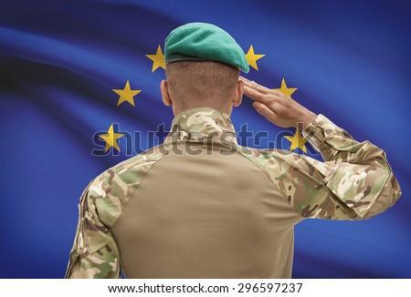 Dark-skinned soldier in hat facing national flag series - European Union - EU - stock photo