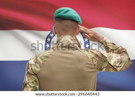 Dark-skinned soldier in hat facing US state flag series - Missouri - stock photo