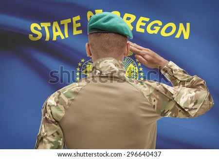 Dark-skinned soldier in hat facing US state flag series - Oregon - stock photo