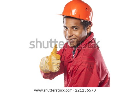 dark-skinned worker with helmet and gloves showing thumbs up - stock photo