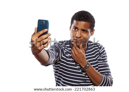 dark-skinned young man making selfie on white background - stock photo