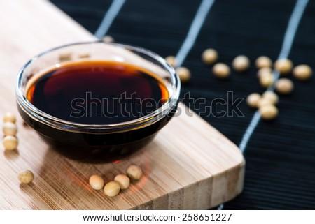 Dark Soy Sauce (close-up shot) on Bamboo background - stock photo