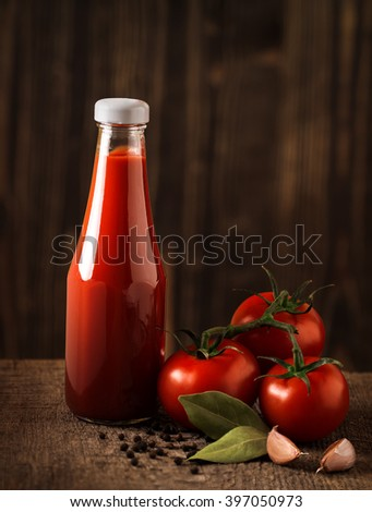 Dark still life with ketchup and ingredients on the rough wood - stock photo