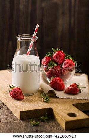 Dark still life with milk and strawberry on rough wood - stock photo