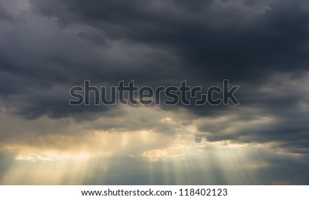 dark storm clouds and sun rays - stock photo