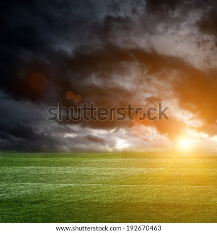 Dark storm clouds over a football field - stock photo