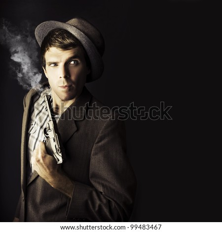 Dark Studio Image Of A Professional Hit Man Wearing Vintage Suit Holding A Retro Hand Gun In A Dangerous Business Conceptual, Isolated On Black Background - stock photo