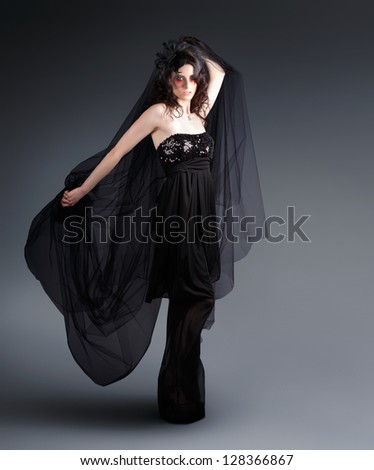 Dark Studio Picture Of An Alternative Fashion Model Wearing Black Lace Dress When Dancing In Creative Make-Up In A Depiction Of A Black Fashion Movement - stock photo