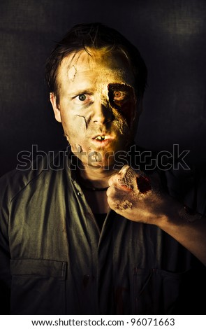 Dark Studio Portrait Of A Rotten And Mangled Zombie Raising A Clench Fist With A Deadly Intense Gaze During A Fight Of The Living Dead - stock photo