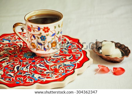 Dark turkish coffee on table with patterned ceramic tray and sugar basin at cafeteria  - stock photo