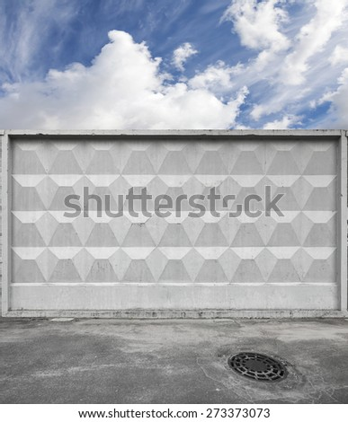 Dark urban road pavement with sewage manhole and blue sky behind gray concrete fence - stock photo