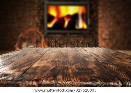 dark wall with black fireplace with wooden table place  - stock photo