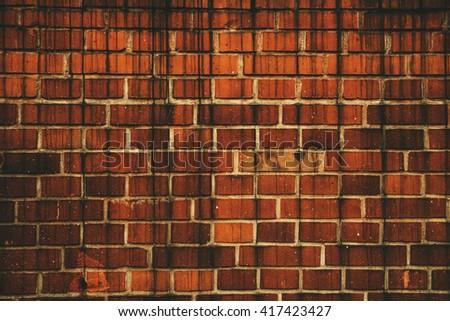 Dark weathered worn factory brick wall background.  - stock photo