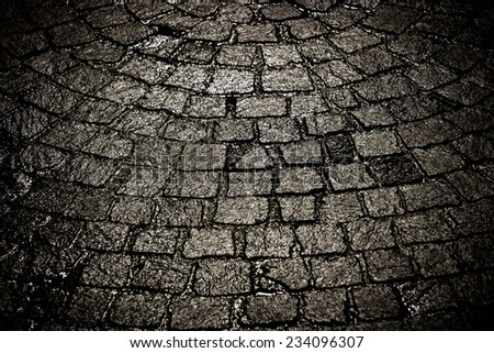 Dark wet cobblestone background, tight view. High contrast and desaturated. - stock photo