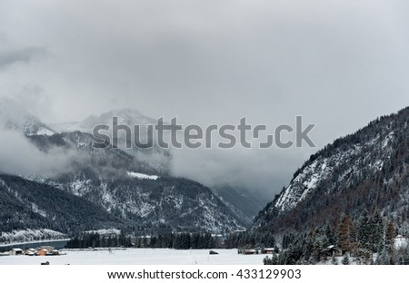 Dark winter clouds looming over snow covered mountains partially covered by snow - stock photo