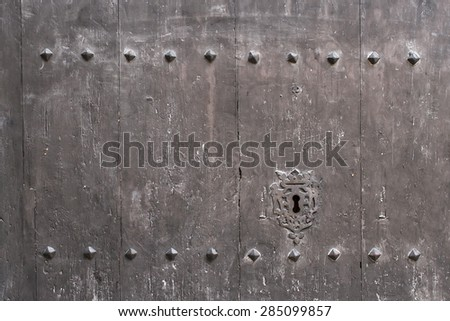 Dark wooden door background with vintage metal rivets and keyhole  - stock photo