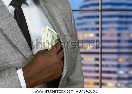 Darkskinned businessman hiding american dollars. Rich official on evening background. Owner of luxury hotel. Man has to earn. - stock photo