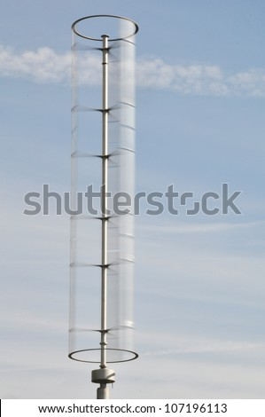 Darrieus type vertical axis windmill against a cloudy blue sky - stock photo