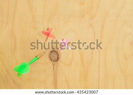 Dart arrows stuck around the center of the target.Dart arrows stuck around the center wood.closeup dart arrow hitting in target bullseye of dartboard, business solutions and success concept - stock photo