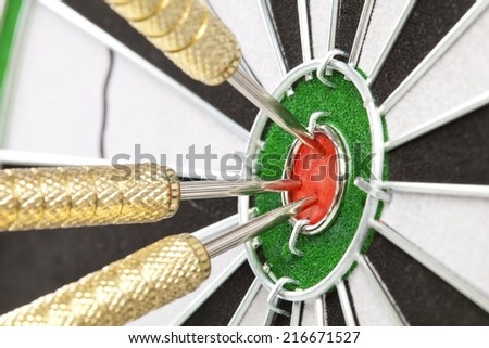 dart board sisal with darts in bullseye - stock photo