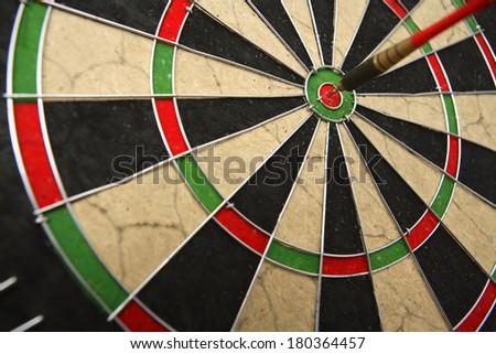 Dart board with dark on bullseye  - stock photo