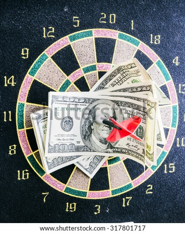 dart Darts accurately hit the target in one hundred dollar bills as a sign of business success - stock photo