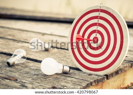 Dart hit the center of dartboard with light bulbs - stock photo