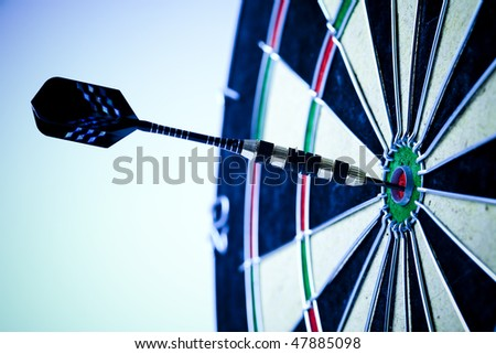 Dart on bulls eye target of dartboard - stock photo