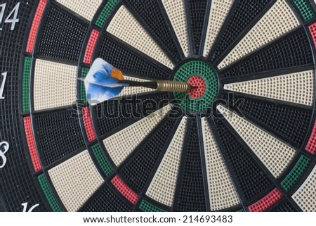 Dart stuck right in the center of the target - stock photo